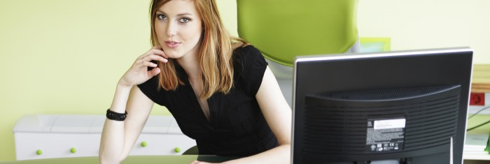 Young gorgeous business woman at desk looking into camera-[iStock_000006663074Large]